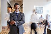 Portrait of middle aged black man in a busy modern workplace poster