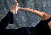 stock photo of bow-legged  - Close up of fit athletic woman doing half bow yoga pose showing arm and leg with hand holding foot in studio against a mottled background - JPG