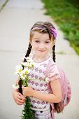 stock photo of bagpack  - Young school girl with pink bagpack and daisies - JPG