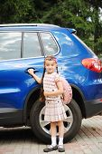 stock photo of bagpack  - Young school girl with pink bagpack waits near the blue car - JPG