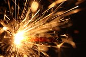 stock photo of guy fawks  - Closeup of a burning sparkler against black background - JPG