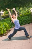 Woman Doing Yoga Posture Warrior 1 Outdoors In Public On Mat
