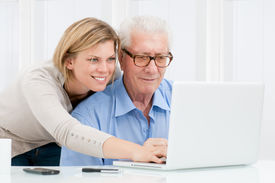 image of computer technology  - Happy smiling young girl teaching and showing new computer technology to her grandfather - JPG