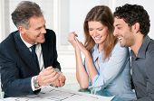 stock photo of real-estate agent  - Happy estate agent showing new home keys to a young couple after a discussion on house plans - JPG