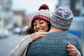 Happy african american girlfriend hugging boyfriend on street with closed eyes. Friends meeting and  poster