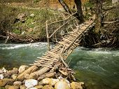 Wooden Old Bridge Across  A River. Wooden Bridge With A Railing On The River Running Water Beginning poster