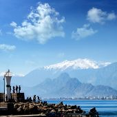 Silhouetted people relaxing in Antalya harbor over blue sky and high mountains poster