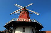 Traditional Netherlands culture of close up red wooden windmill over sunny blue sky poster