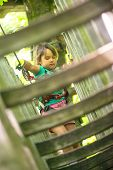Little Girl Climbing In Adventure Park. Girl Enjoys Climbing In The Ropes Course Adventure. poster