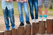 Legs of the teenagers standing on the wooden columns on the playground