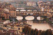 View From The River To The Famous Italian Medieval Bridge - Ponte Vecchio In Florence On Sunset, Tra poster