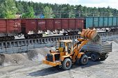 Wheel Loader Loads Gravel Into A Dump Truck At A Cargo Railway Station. Fron-end Loader Unloads Crus poster