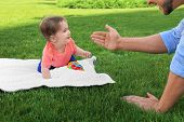 Adorable Little Baby Crawling Towards Father On Blanket Outdoors poster