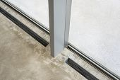 Inserted Radiator In The Polished Concrete Floor. Vertical Mullion Glass Curtain Wall And Windows. poster