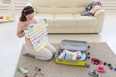 Holidays, Voyage And Travel Concept - Woman Collects A Yellow Suitcase At Home poster