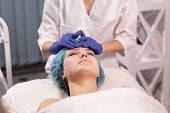 Cosmetologist In Blue Gloves Does Facial Massage. Woman Enjoys The Procedure. Anti-aging Massage. Co poster