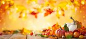 Autumn background from fallen leaves and pumpkins on wooden vintage table. Autumn concept with red-y poster
