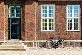 Exterior Architecture. Vintage Bicycles In Front Of Brick Facace In Copenhagen, Denmark. poster