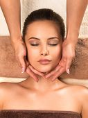 Portrait of beautiful young healthy woman relaxing and getting head massage in the spa salon. poster