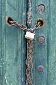 Locks And A Padlock And Chain On An Old House Door With Peeling Paint poster
