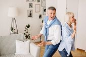 Playful Mature Couple Dancing Active Dance At Home, Having Fun At Retirement, Free Space poster