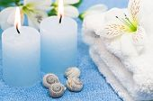 Blue spa candles with seashells, towel and decoration flowers