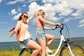 leisure and friendship concept - happy smiling teenage girls or friends riding bicycle together at s poster