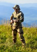 Army Forces. Ready To Shoot. Hunter Hold Rifle. Hunter Mountains Landscape Background. Focus And Con poster