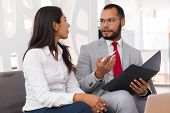 Mentor Explaining Document Specifics To Intern. Business Man And Woman Sitting On Office Couch With  poster
