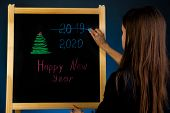 Change Of Year From 2019 To 2020. Inscription Happy New Year On Black Board. Black Board With Hand I poster