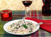Beef Stroganoff And Egg Noodles With Wine And A Lit Candle.