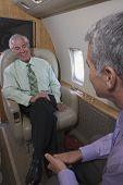 Businessmen talking onboard an airplane