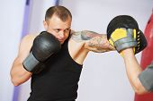 foto of boxing  - boxer man during boxing hiting mitts at training fitness gym - JPG