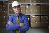 Businessman wearing hard hat in warehouse