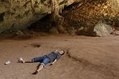 stock photo of cave woman  - Alone woman sleeping on ground in tropical cave - JPG