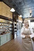Retrato de una situación mercantil especia femenino senior feliz con los brazos cruzados en la tienda