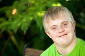 Portrait Of Cute Handicapped Boy In Garden.