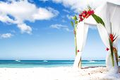 stock photo of cabana  - wedding arch decorated with flowers on beach - JPG