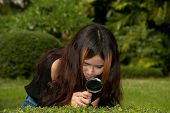 Pretty Asian Woman With Magnifying Glass .