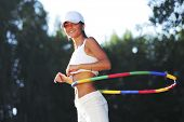woman rotates hula hoop on nature background