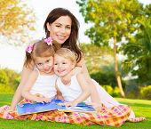 Picture of young happy family, beautiful mother with two cute kids having fun outdoors in spring, pr