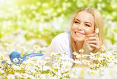 Image of pretty woman lying down on chamomile field, happy female holding in hand beautiful white flower, cheerful girl resting on daisy meadow, relaxation outdoor in springtime, vacation concept