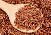 stock photo of flax seed oil  - close up of flax seeds and wooden spoon food background - JPG