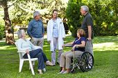 Geriatric nurse with senior group in garden of a retirement home