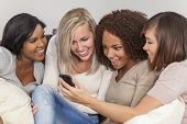 Interracial group of three beautiful young women girl friends at home sitting together on a sofa smiling, surprised and shocked using cell phone smartphone