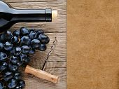 Wine Bottle, Corkscrew And Grape On Wooden Background