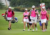 KUALA LUMPUR - OCTOBER 12: Stacy Lewis and Caroline Masson with caddies walk to the 2nd hole green of the KLGCC course on Day 3 of the Sime Darby LPGA on October 12, 2013 in Kuala Lumpur, Malaysia.