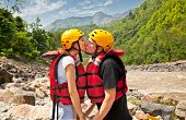 stock photo of raft  - Man and woman kissing for good lack before a rafting on river in Nepal - JPG