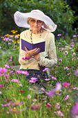 Elegant Elderly Lady Reading In Her Garden