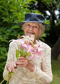 Happy Elderly Lady With Fresh Lilies